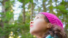 A little girl looks around and then looks up at the sky while in a forest Stock Footage