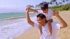 A father gives his son a ride on his shoulders while they play at the beach Stock Footage