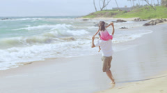 A father runs around the beach with his daughter on his shoulders Stock Footage
