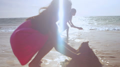 A young girl builds a sand castle at the beach with her sister Stock Footage