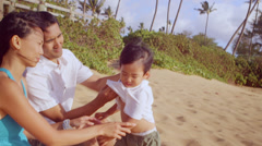 A mother and father clean their sons nose while sitting at the beach Stock Footage