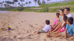 A family sits in the sand at the beach and look out to the ocean at dusk Stock Footage