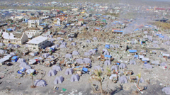 Aerial of refugee tents in midst the destroyed town Stock Footage
