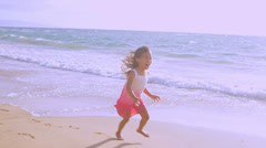 A girl runs down the beach and into her father's arms Stock Footage