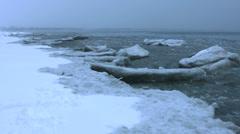 Icy Shore - waves break pieces off the shoreline Stock Footage
