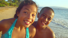 A young brother and sister at the beach smile into the camera - stock footage