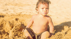 A young boy lays in the sand and wiggles around on the beach Stock Footage