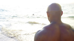 A father and son build sandcastles together at the beach Stock Footage
