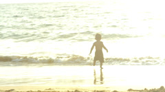 A young boy runs towards the ocean and jumps into the waves Stock Footage