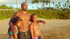 A dad stands with his son and daughter at the beach looking out to the horizon Stock Footage