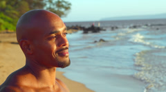 A man stands on the beach and looks out over the ocean Stock Footage
