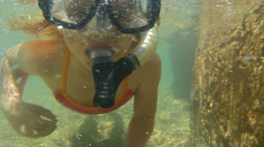 An adorable little girl looks at the camera while she swims with snorkel gear on Stock Footage