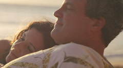 A woman rests her head on her boyfriend's chest on the beach Stock Footage