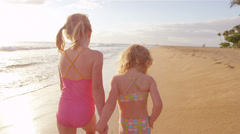 Two sisters walk down the beach together swinging their arms back and forth Stock Footage