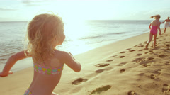 Young girls on a beach run to there mom and give her a big hug as the sun sets Stock Footage