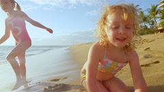 A little girl has fun playing in the waves as the splash on her. Close up shot. Stock Footage
