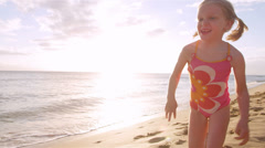 A cute girl runs down the beach with the sun setting behind her. Close up shot. Stock Footage