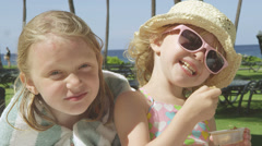 Two little sisters smile as the youngest eats a snack on a beautiful day Stock Footage