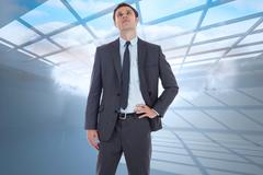 Stock Illustration of Composite image of serious businessman with hand on hip