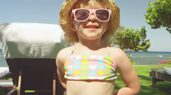 A young girl plays with a flower while at the beach Stock Footage