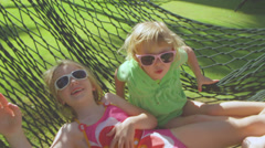 Two little sisters in a hammock swings back and forth on the beach Stock Footage