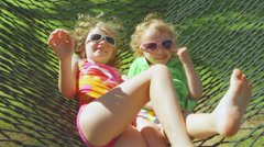 Two adorable little girls lie on a hammock together as it swings back and forth - stock footage