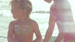 Two adorable sisters mess around and hug each other while at the beach together Stock Footage
