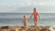 Stock Video Footage of Two little sisters lie on the beach together and smile for the camera
