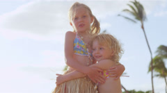 Little girls dressed in their hula dresses give each other a hug after dancing Stock Footage