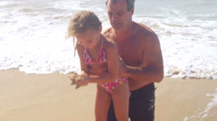 A father gives his daughter a ride on his shoulders while they play at the beach Stock Footage