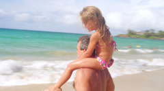 A father gives his daughter a ride on his shoulders at the beach Stock Footage