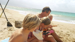 A family sits in the sand at the beach and play ukulele and blow conch shells Stock Footage