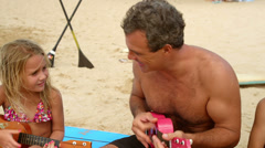 A father plays ukulele with her daughter while sitting at the beach Stock Footage