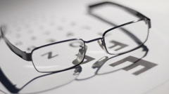Shadows playing across glasses and eyetest chart Stock Footage