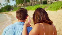 Two children run down the beach and into their parent's arms Stock Footage