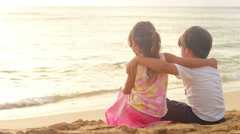 A young brother and sister with their arm around each other sit on a beach Stock Footage