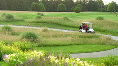 Two golfers driving a golf cart to their next tee off - stock footage