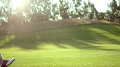 A male golfer walks through the frame while on the fairway Stock Footage