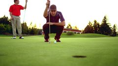 A man squares up and hits a golf shot off the tee Stock Footage