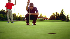 A man lines up a putt as his friend watches and takes the shot Stock Footage