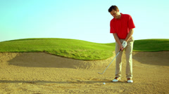 A man hits a golf ball out of a sand trap Stock Footage