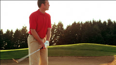 A golfer finds himself hitting out of a sand trap as the sun sets - stock footage