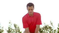 A man in a red shirt squares up and hits a golf shot off the tee - stock footage
