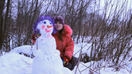 Stock Video Footage of a little girl playing with snowman