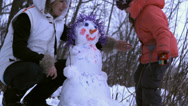 Stock Video Footage of woman (mother) and a little girl playing with snowman