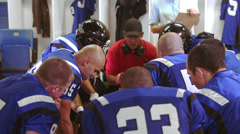 A football team gets a talk from coach in the locker room and jump up excited - stock footage