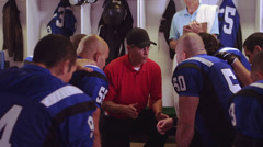 Football players sit in a circle in the locker room and coach gives a speech - stock footage