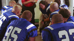 Stock Video Footage of Football team gets a talk in the locker room from a coach