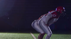 A quarterback receives ball snap and then gets sacked by a defender - stock footage