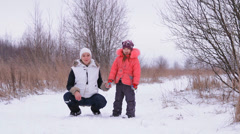 The girl and the baby have fun in the winter nature Stock Footage